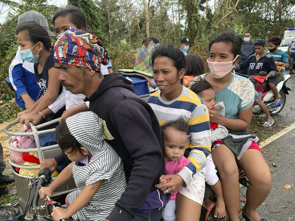Residents evacuate to safer grounds in Pola town on the island of Mindoro, central Philippines, Monday, Oct. 26, 2020. A fast-moving typhoon forced th...