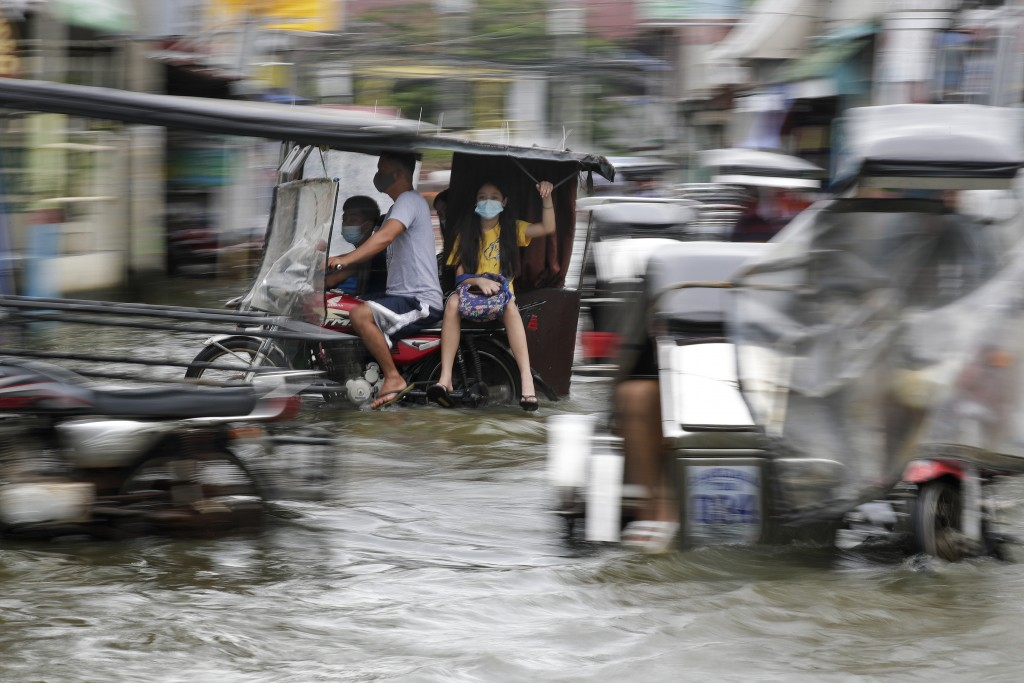 Residents wearing masks to prevent the spread of the coronavirus ride motorcycles as they negotiate a flooded road due to Typhoon Molave in Pampanga p...