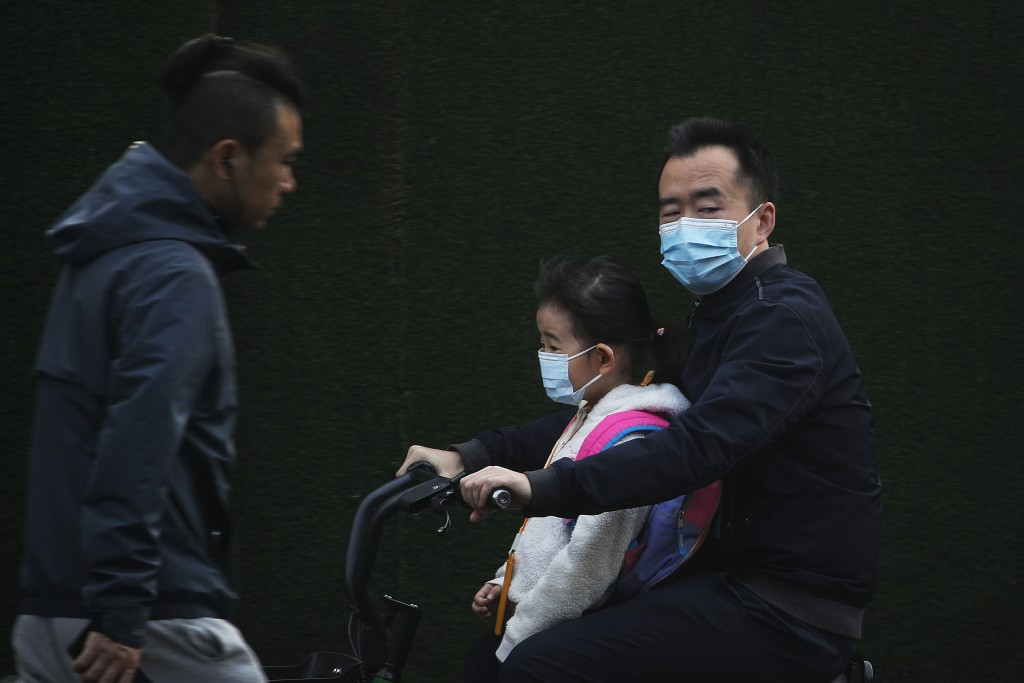 A man and a child, both wearing face masks to help curb the spread of the coronavirus ride on an electric-powered scooter in Beijing, Monday, Oct. 26,...