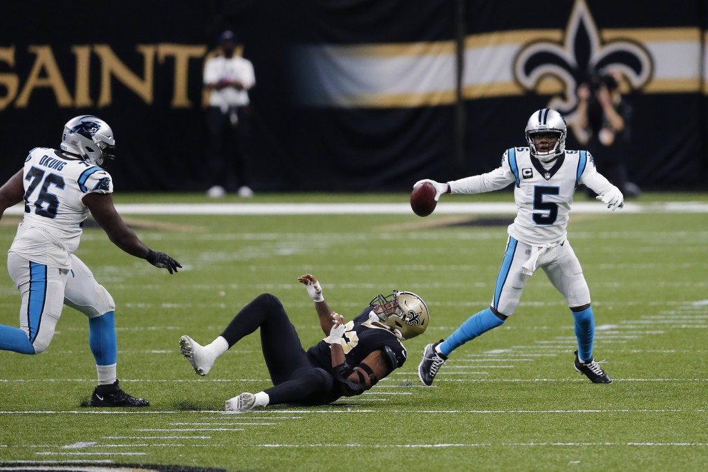 Carolina Panthers quarterback Teddy Bridgewater (5) scrambles past New Orleans Saints defensive end Marcus Davenport as offensive tackle Russell Okung...