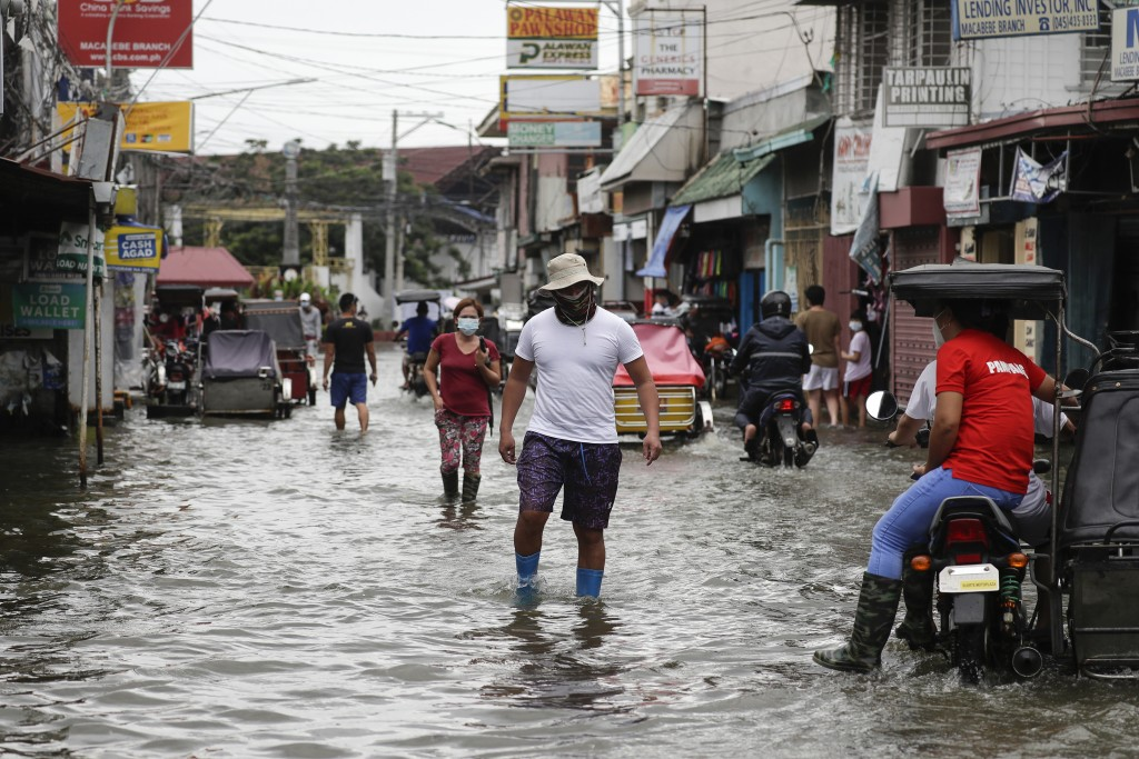 Residents wearing masks to prevent the spread of the coronavirus wade through a flooded road from Typhoon Molave in Pampanga province, northern Philip...