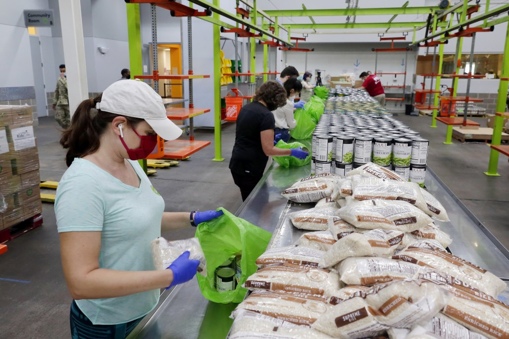 Volunteers load non perishable foods green grocery bag that are then boxed up and put on a pallet for distribution to a school student food program in...