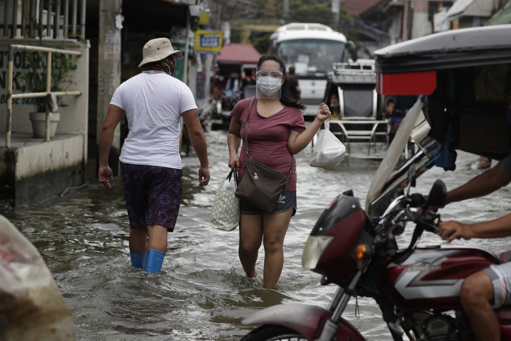 A woman wearing masks to prevent the spread of the coronavirus wades along a flooded road due to Typhoon Molave in Pampanga province, northern Philipp...