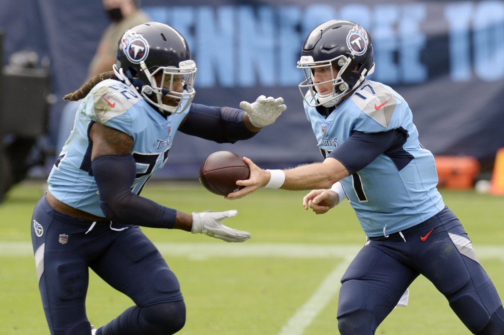 Tennessee Titans quarterback Ryan Tannehill (17) hands the ball off to running back Derrick Henry (22) in the first half of an NFL football game again...