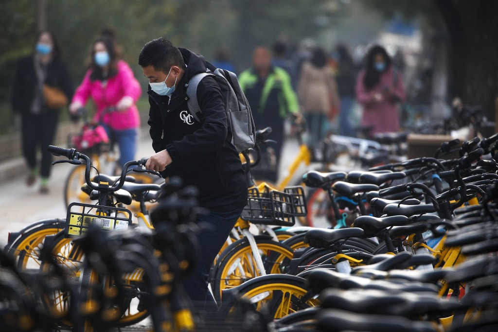 Commuters wearing a face mask to help curb the spread of the coronavirus ride bicycles of bike-sharing companies parked outside a subway station durin...
