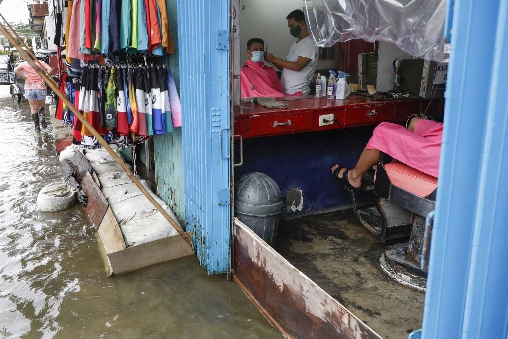 A man has his hair cut at a barbershop flooded by Typhoon Molave in Pampanga province, northern Philippines on Monday, Oct. 26, 2020. The fast moving ...