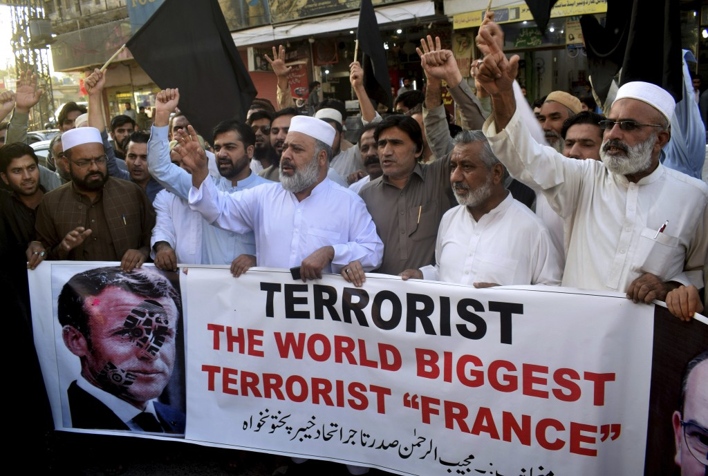 Pakistan traders hold a banner with a defaced picture of French President Emmanuel Macron during a protest against the publishing of caricatures of th...