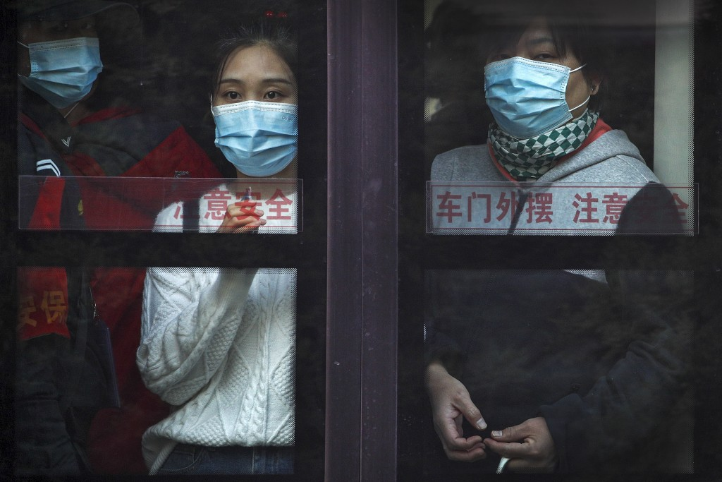 Commuters wearing face masks to help curb the spread of the coronavirus look out from a traveling bus during the morning rush hour in Beijing, Monday,...