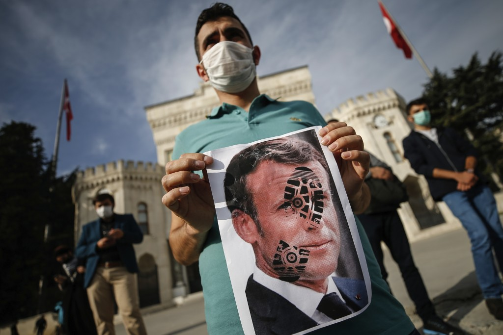A youth holds a photograph of France's President Emmanuel Macron, stamped with a shoe mark, during a protest against France in Istanbul, Sunday, Oct. ...