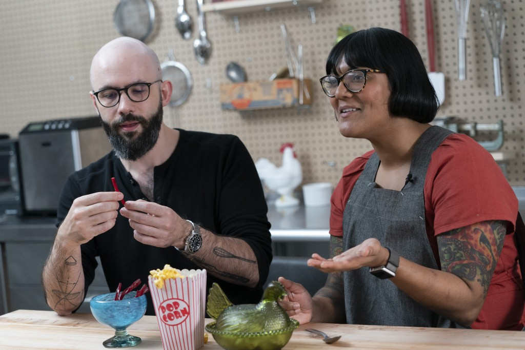 In this Oct. 7, 2020 photo, Andrew Rea, founder of the Binging with Babish network, left, tastes a beet parsnip licorice created by chef Sohla El-Wayl...
