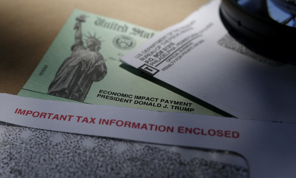 FILE - In this April 23, 2020, file photo, President Donald Trump's name is seen on a stimulus check issued by the IRS to help combat the adverse econ...
