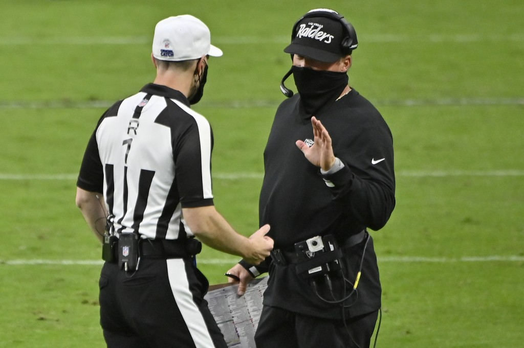 Las Vegas Raiders head coach Jon Gruden, right, speaks with an official during the second half of an NFL football game against the Tampa Bay Buccaneer...