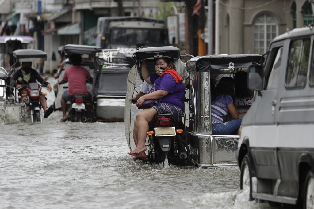 A woman wearing a mask to prevent the spread of the coronavirus rides a motorcycle as they pass a flooded street due to Typhoon Molave in Pampanga pro...
