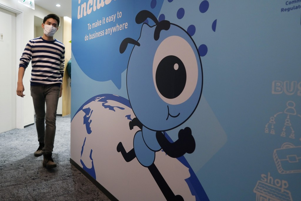 In this Friday, Oct. 23, 2020, photo, an employee walks past a graphic of the Ant Group's mascot at their office in Hong Kong. The world's largest fin...