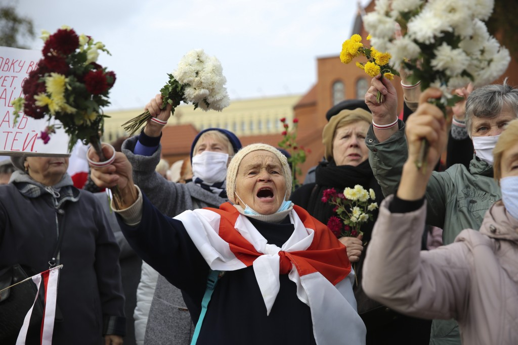 People, most of them pensioners, wave bunches of flowers during an opposition rally to protest the official presidential election results in Minsk, Be...