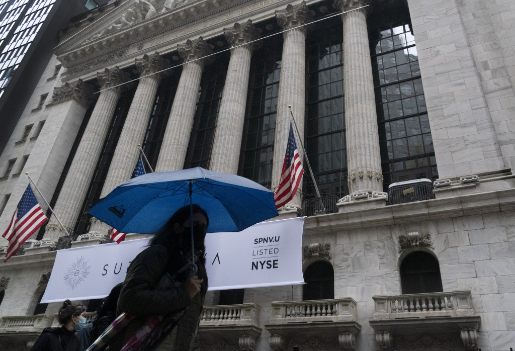 A woman with an umbrella passes the New York Stock Exchange, Monday, Oct. 26, 2020. U.S. stocks are drifting Tuesday, Oct. 27, 2020, as momentum slows...