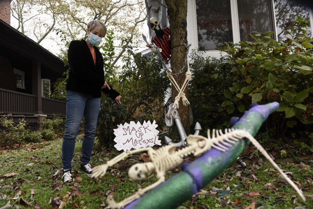 Carol McCarthy poses next to pirate-themed Halloween decorations reminding people to mask up while trick-or-treating during the COVID-19 pandemic, Mon...