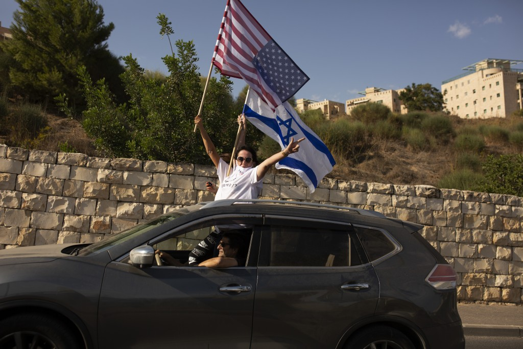 Supporters of U.S. President Donald Trump for re-election wave an American and an Israeli flag from a car headed for a rally outside of the U.S. Embas...