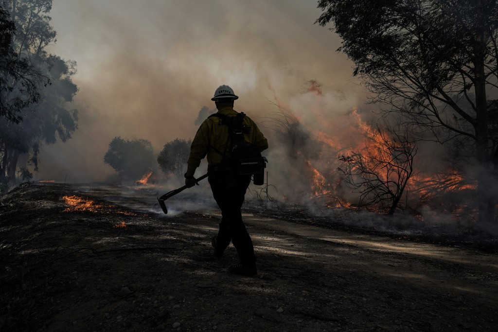 A firefighter prepares to put out hotspots while battling the Silverado Fire, Monday, Oct. 26, 2020, in Irvine, Calif. The fast-moving wildfire forced...