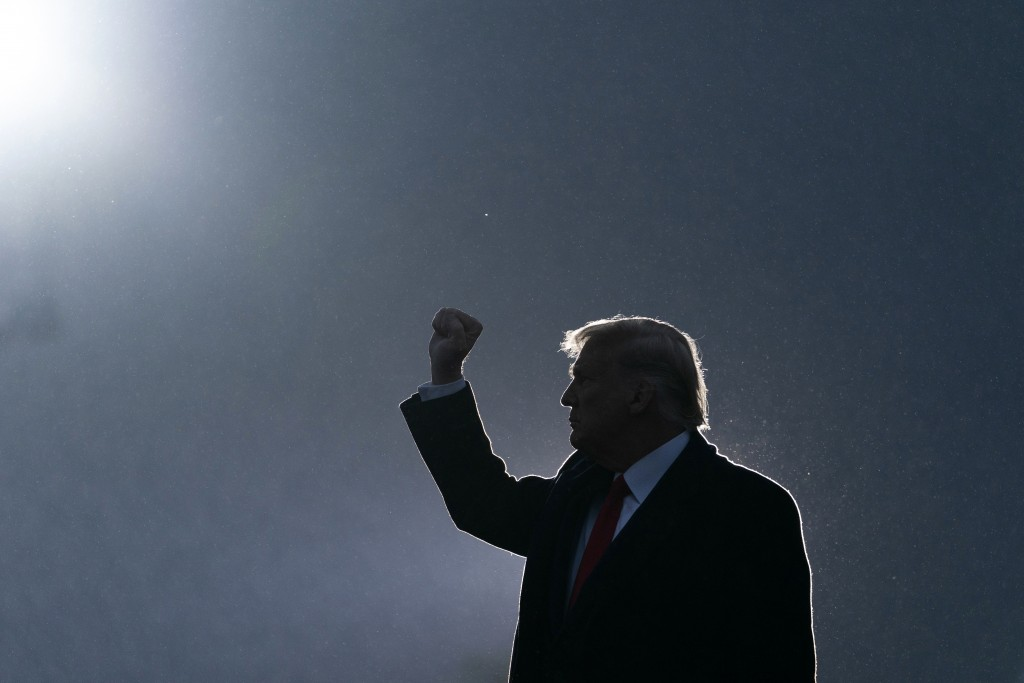 President Donald Trump pumps his fist as he departs after speaking at a campaign rally at Altoona-Blair County Airport, Monday, Oct. 26, 2020, in Mart...