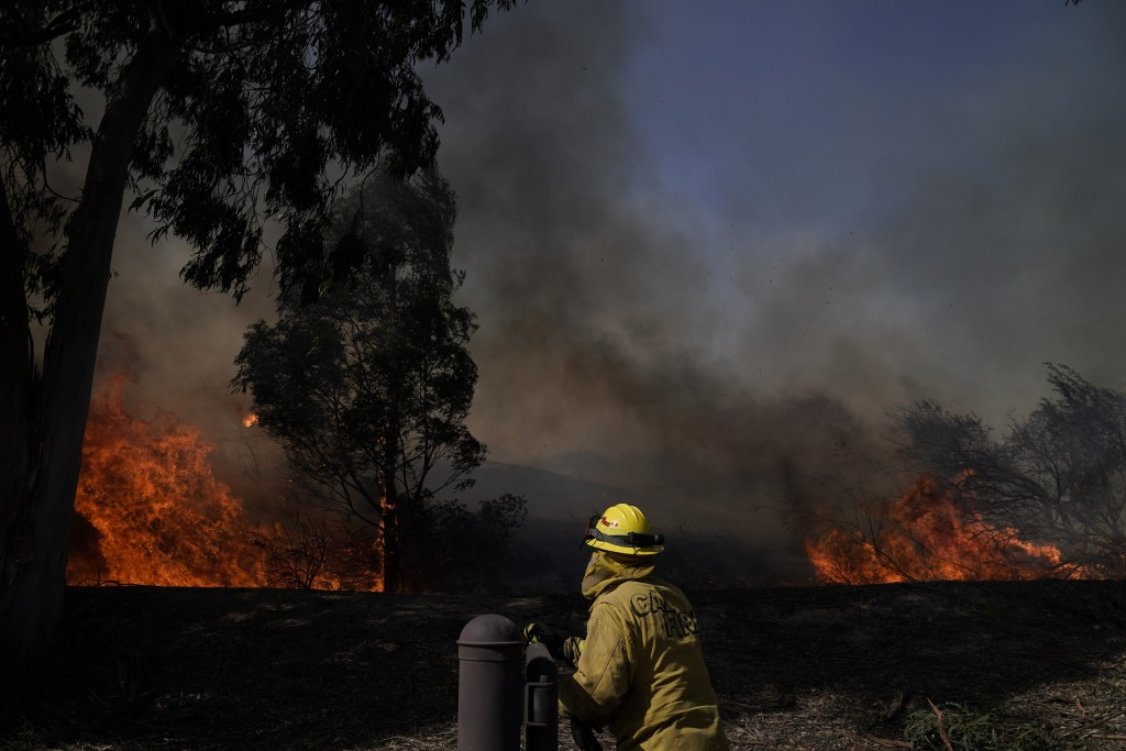 A firefighter watches flames from the Silverado Fire, Monday, Oct. 26, 2020, in Irvine, Calif. A fast-moving wildfire forced evacuation orders for 60,...