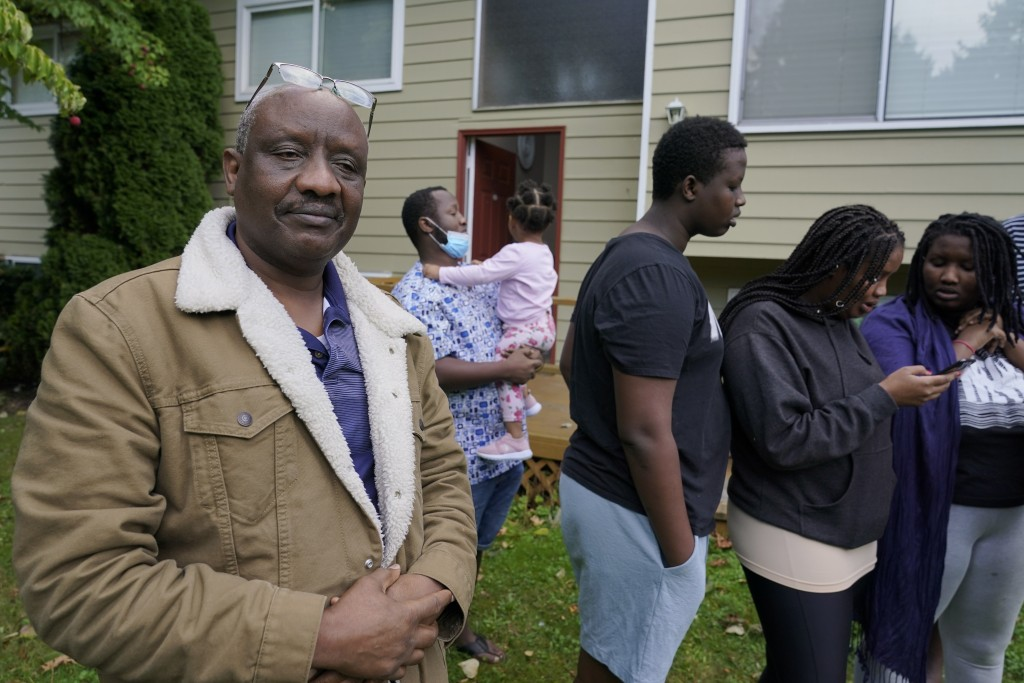 Sophonie Bizimana, left, a permanent U.S. resident who is a refugee from Congo, stands in front of his home in Kirkland, Wash., Wednesday, Oct. 14, 20...