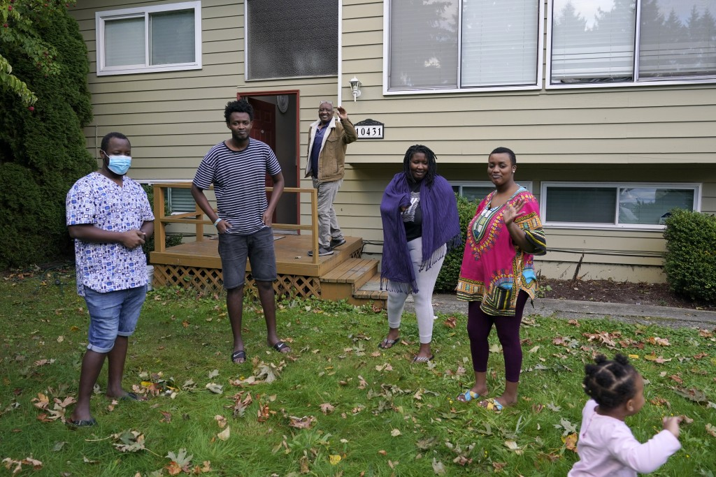Sophonie Bizimana, center, a permanent U.S. resident who is a refugee from Congo, waves from the steps of his home in Kirkland, Wash., Wednesday, Oct....