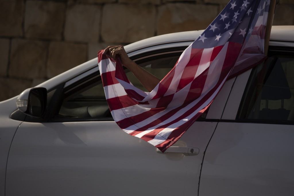 An Israeli supporter of U.S. President Donald Trump for re-election waves an American flag from her car as she headed for a rally outside of the U.S. ...