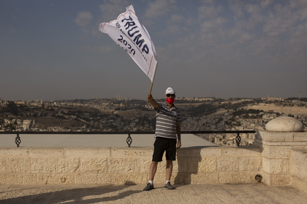 An Israeli supporter of U.S. President Donald Trump waves a campaign flag at a rally for his re-election, on a promenade overlooking Jerusalem, Tuesda...
