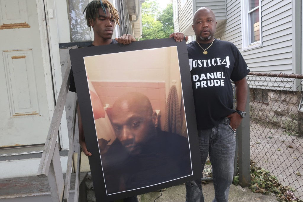 FILE - In this Sept. 3, 2020, file photo, Joe Prude, brother of Daniel Prude, right, and his son Armin, stand with a picture of Daniel Prude in Roches...