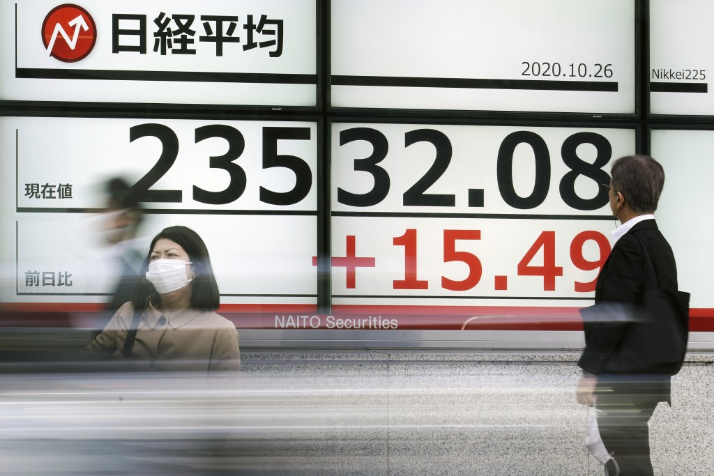 Pedestrian stand near an electronic stock board showing Japan's Nikkei 225 index at a securities firm in Tokyo Monday, Oct. 26, 2020. Asian shares wer...