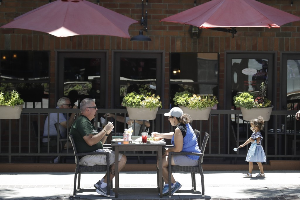 FILE - In this July 18, 2020 file photo, patrons eat at a table set up on a sidewalk in Burbank, Calif. California's financially battered restaurants ...