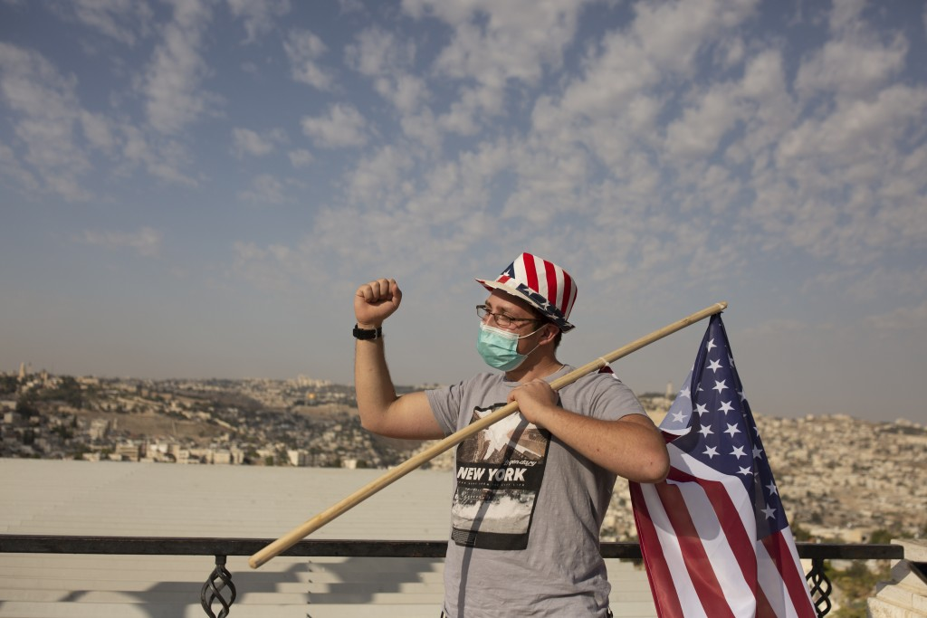 An Israeli supporter of U.S. President Donald Trump wears a hat in the colors of the American flag at a rally for his re-election, at a promenade over...