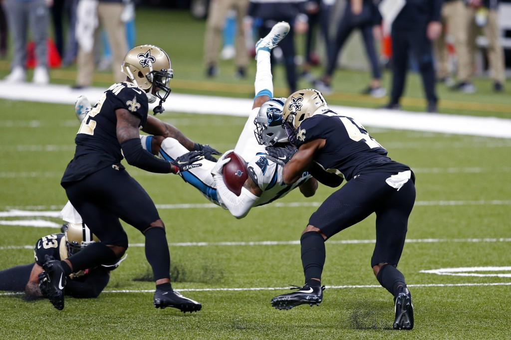 Carolina Panthers wide receiver Robby Anderson is upended by New Orleans Saints safety Chauncey Gardner-Johnson, left, and free safety Marcus Williams...