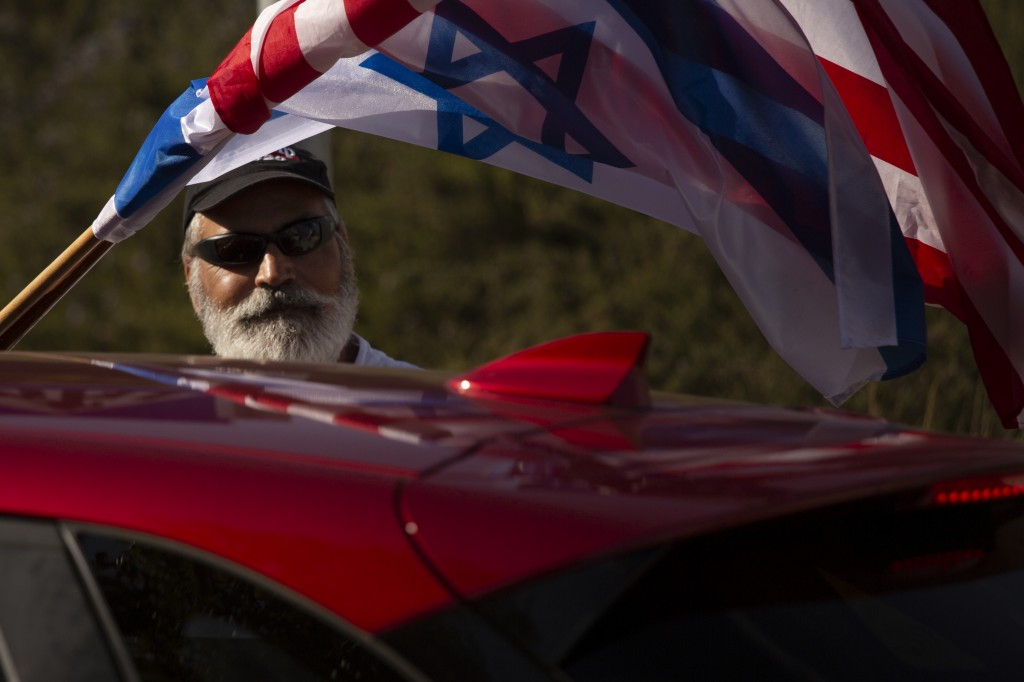 An Israeli supporter of the re-election of U.S. President Donald Trump waves American and Israeli flags from a car at a rally outside of the U.S. Emba...