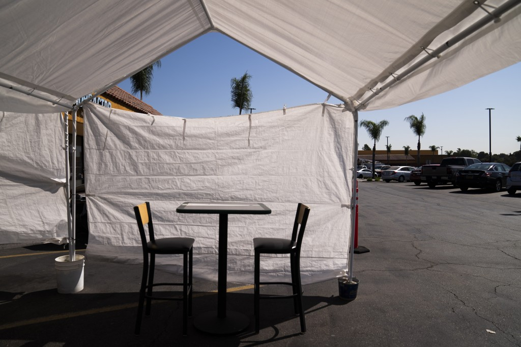 FILE - In this Sept. 30, 2020 file photo, a table, and chairs are set up in the outdoor dining area of a restaurant at a strip mall in La Mirada, Cali...