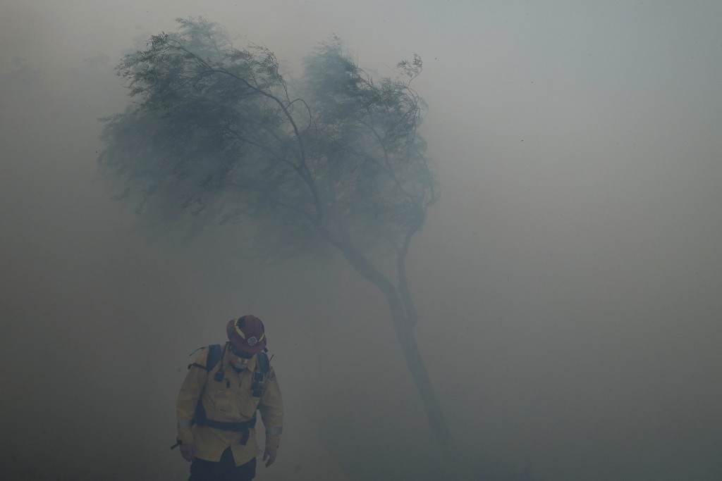 A firefighter braves gusty winds as heavy smoke from the Silverado Fire fills the air, Monday, Oct. 26, 2020, in Irvine, Calif. A fast-moving wildfire...