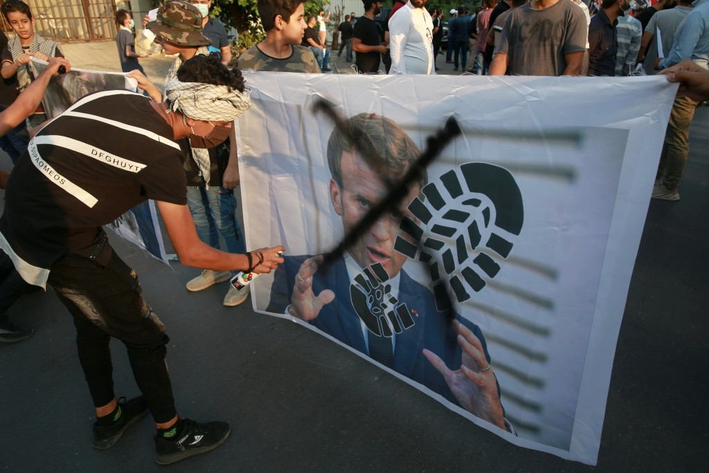 Protesters deface a picture of French President Emmanuel Macron during a protest over caricatures of the Prophet Muhammad they deem insulting and blas...