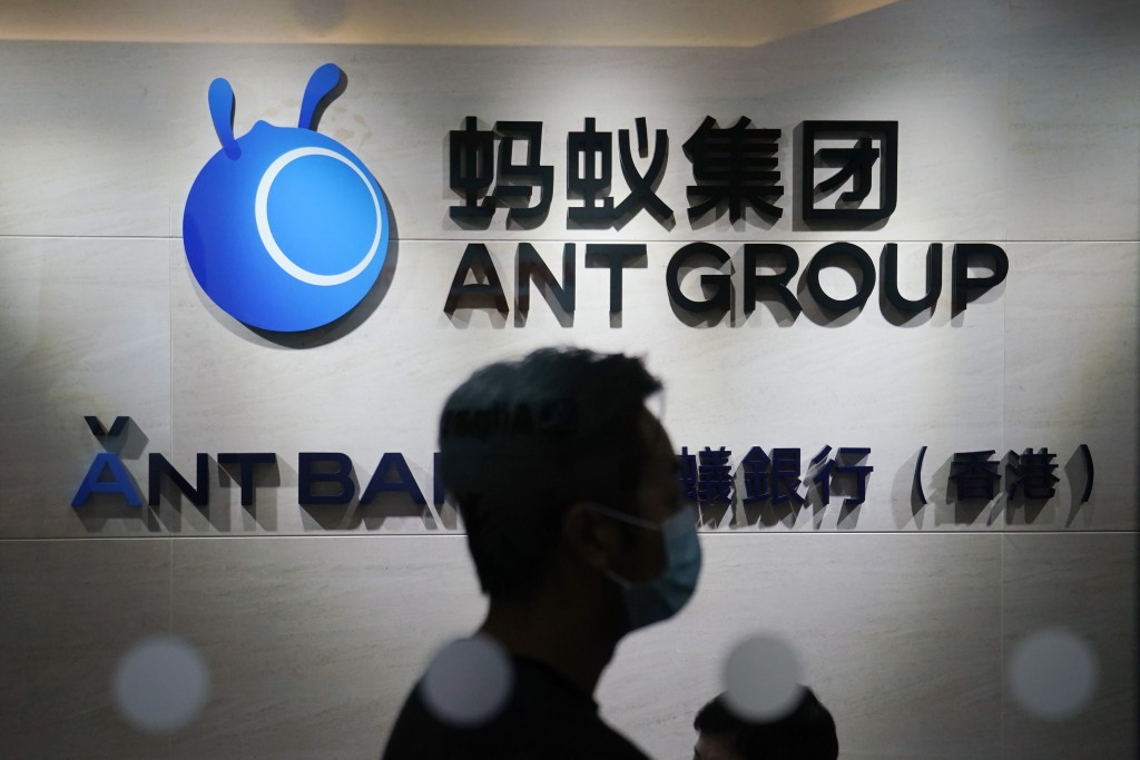 In this Friday, Oct. 23, 2020, photo, an employee walks past a logo of the Ant Group at their office in Hong Kong. The world's largest fintech company...