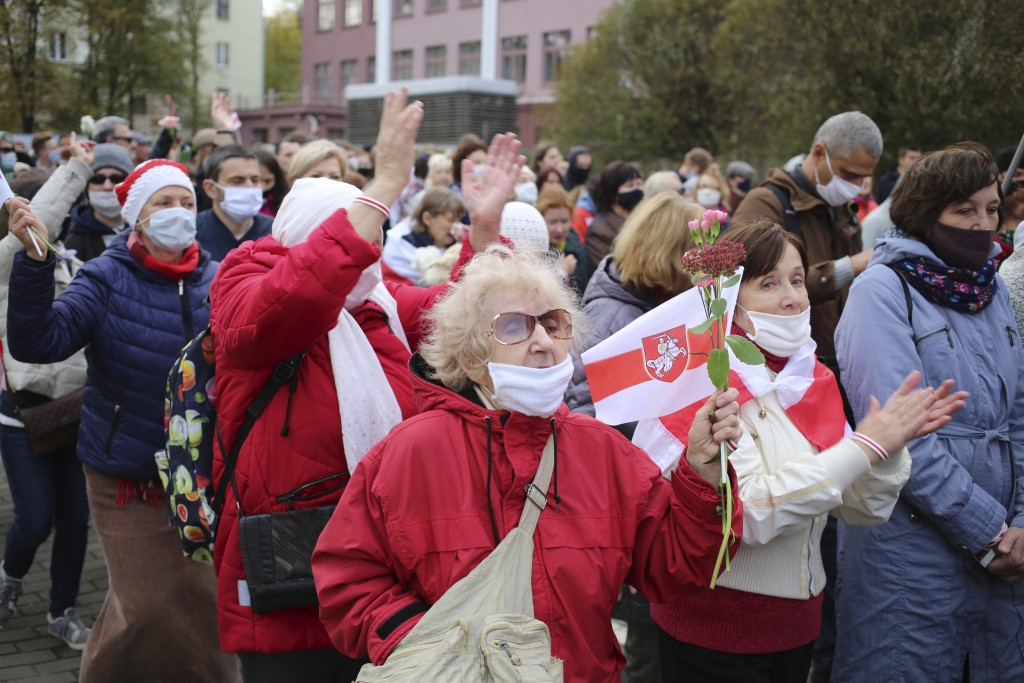 People, most of them pensioners, hold old Belarusian national flags march during an opposition rally to protest the official presidential election res...