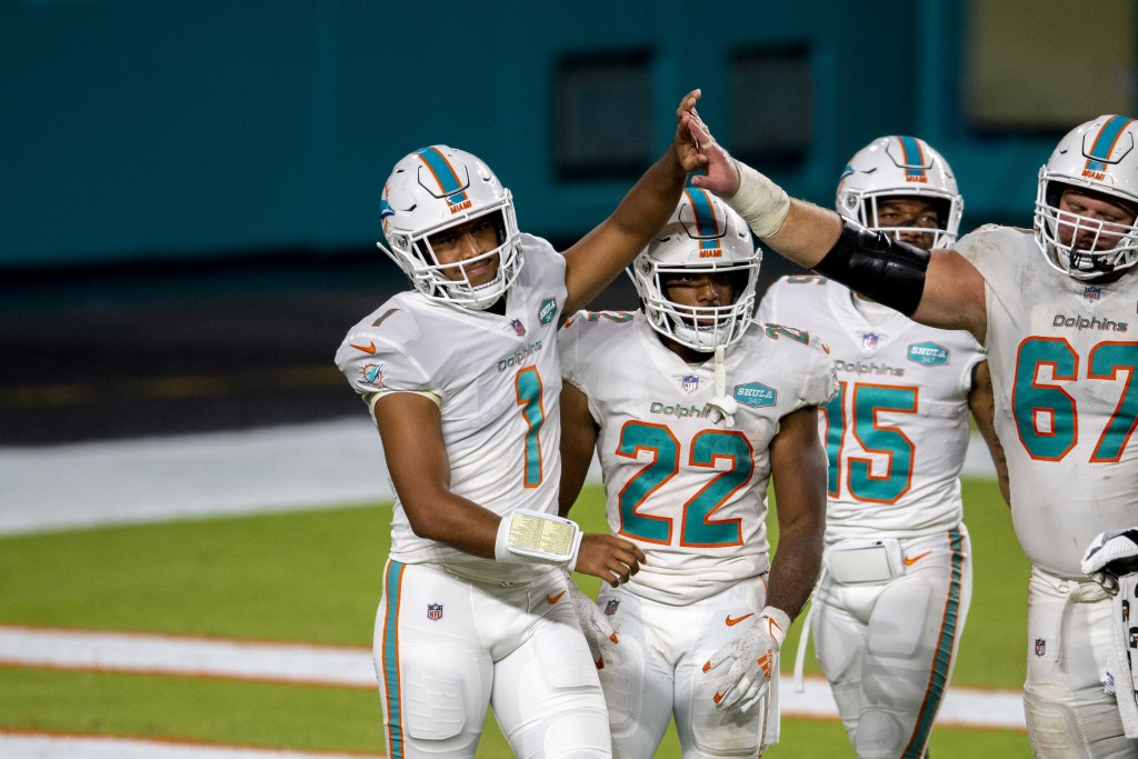 Miami Dolphins quarterback Tua Tagovailoa (1) celebrates his first NFL play with Miami Dolphins running back Matt Breida (22), Miami Dolphins guard Te...