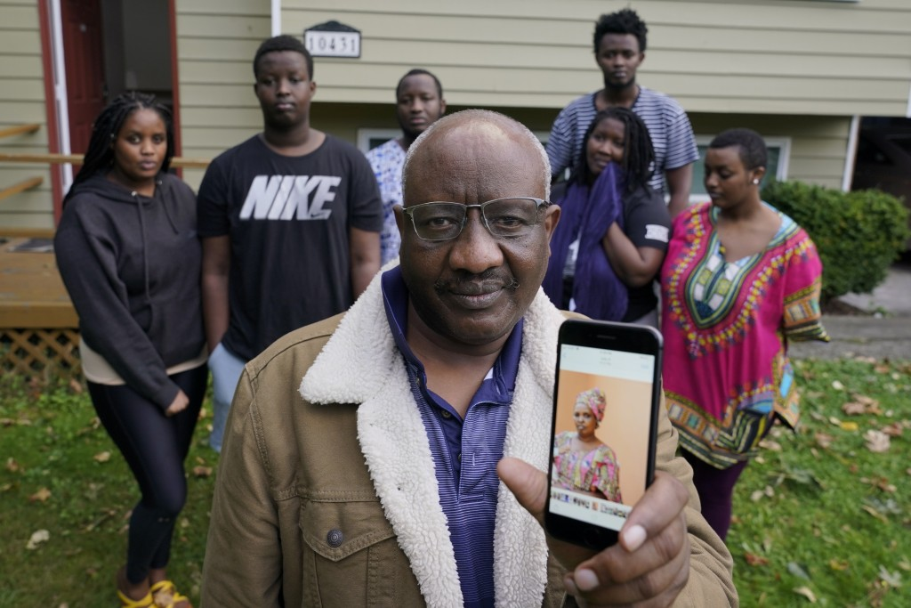Sophonie Bizimana, center, a permanent U.S. resident who is a refugee from Congo, poses for a photo, Wednesday, Oct. 14, 2020, at his home in Kirkland...