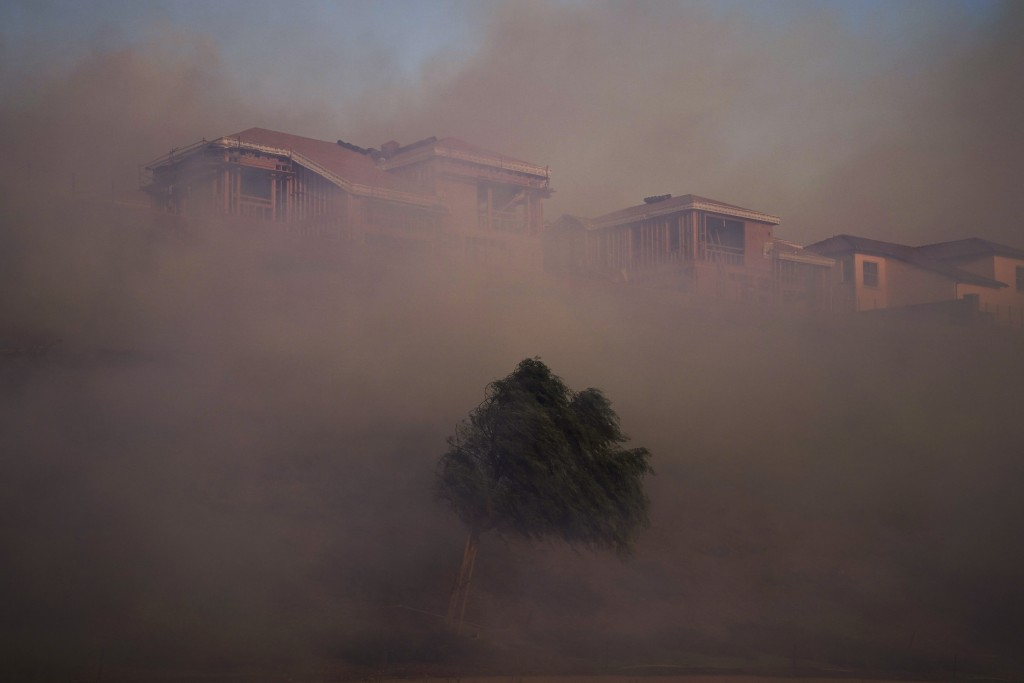 Gusting winds carry smoke from the Silverado Fire into residential areas Monday, Oct. 26, 2020, in Irvine, Calif. A fast-moving wildfire forced evacua...