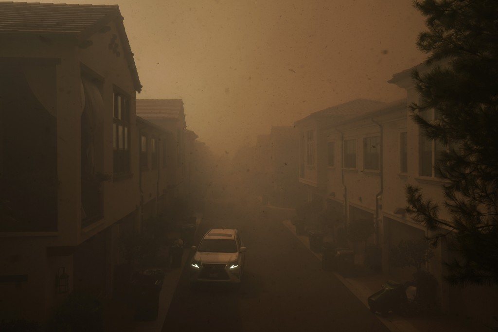 An SUV is parked in the evacuated residential area filled with heavy smoke from the Silverado Fire Monday, Oct. 26, 2020, in Irvine, Calif. A fast-mov...