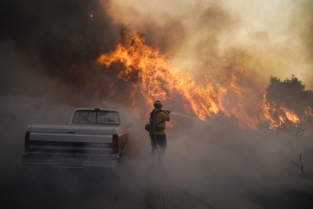 Firefighter Raymond Vasquez battles the Silverado Fire Monday, Oct. 26, 2020, in Irvine, Calif. A fast-moving wildfire forced evacuation orders for 60...
