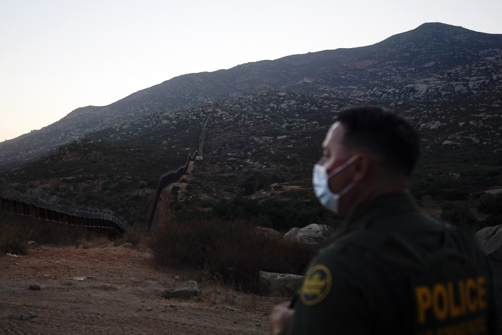 Border Patrol agent Justin Castrejon looks toward where the border wall makes its way over a mountain Thursday, Sept. 24, 2020, near Tecate, Calif. Pr...