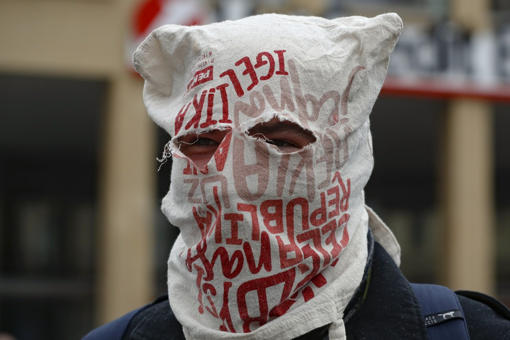 A man wears a bag over his head instead of a mask as demonstrators gather to protest the COVID-19 preventive measures downtown Prague, Czech Republic,...