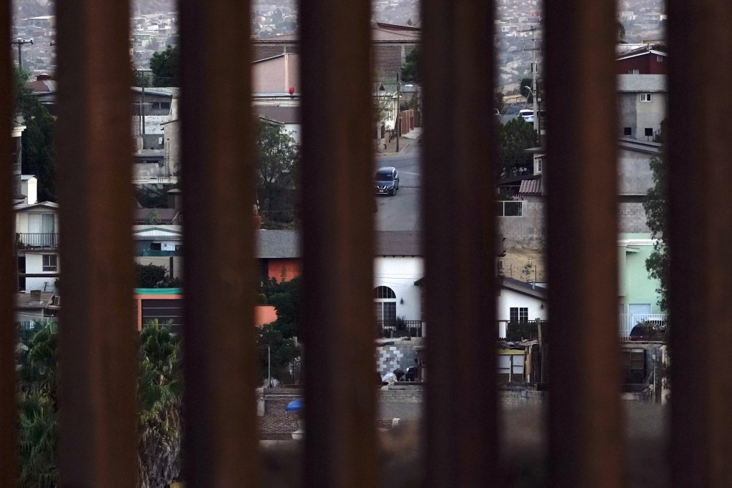 Houses in Tecate, Mexico are seen through a new section of border wall Thursday, Sept. 24, 2020, near Tecate, Calif. President Donald Trump's reshapin...