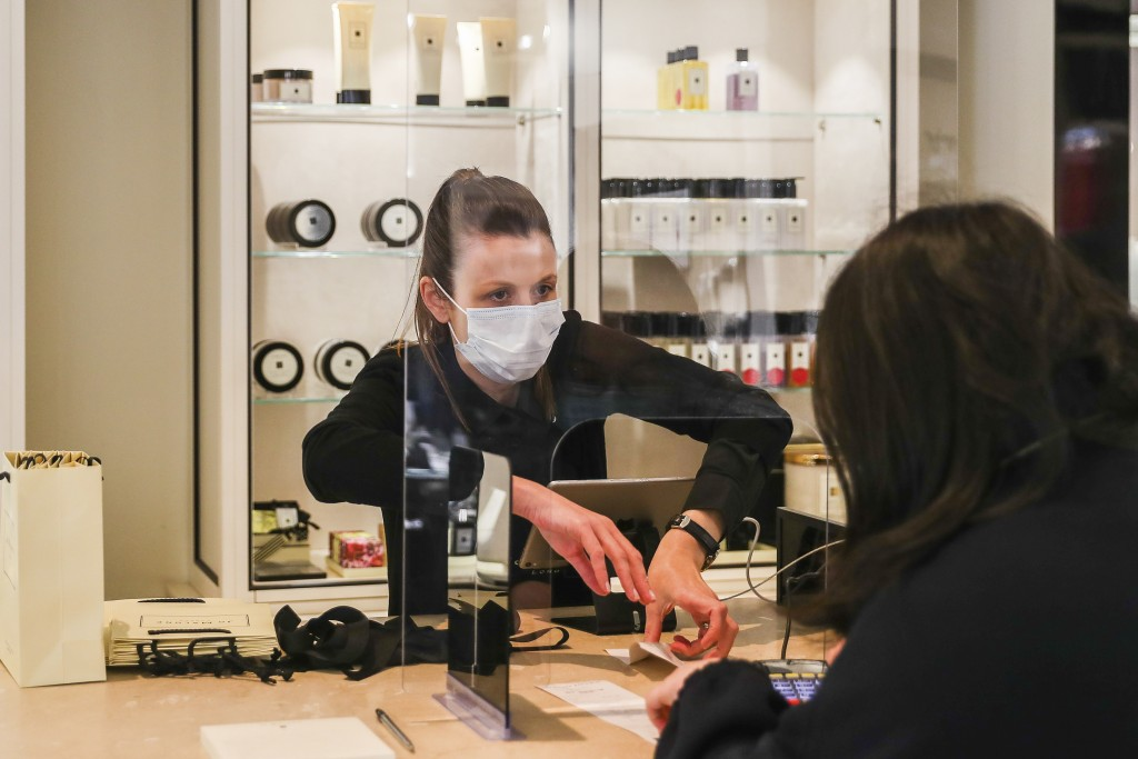 A retail worker wearing a face mask serves a customer behind a shield as she processes a sale at a large retail department store in Melbourne, Austral...