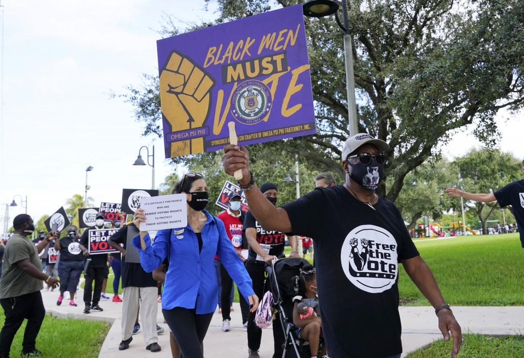 Supporters of restoring Florida felons' voting rights march to an early voting precinct, Saturday, Oct. 24, 2020, in Fort Lauderdale, Fla. The Florida...